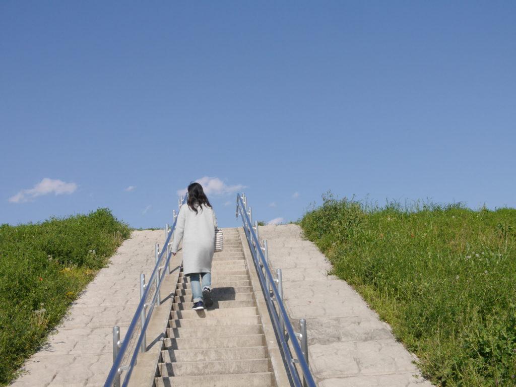 青空に向かう土手の階段を上る女性