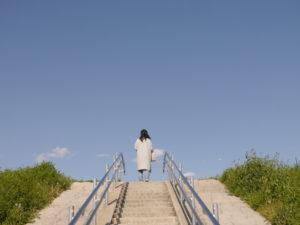 土手の階段と青空と女性