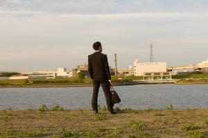 川を眺めるサラリーマン