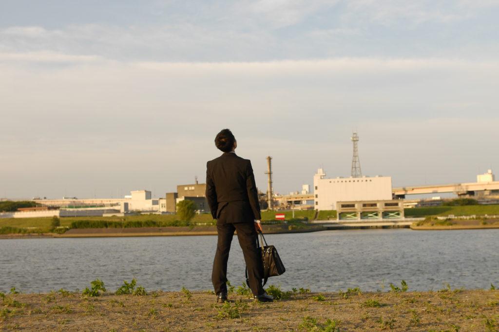 川辺で空を見るサラリーマン