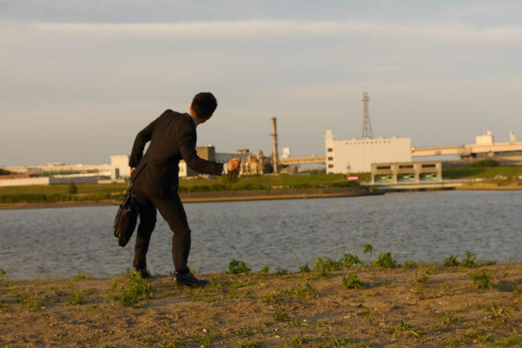 川に石を投げるサラリーマン